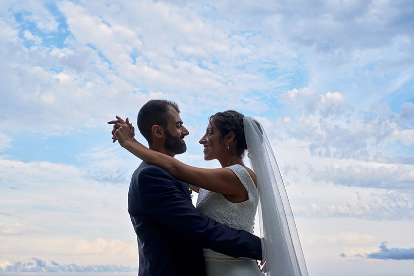 bride and groom under a cloudy blue sky